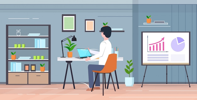 Student sitting at desk using laptop guy analyzing statistic data on flip chart e-learning education concept modern cabinet interior  full length rear view horizontal