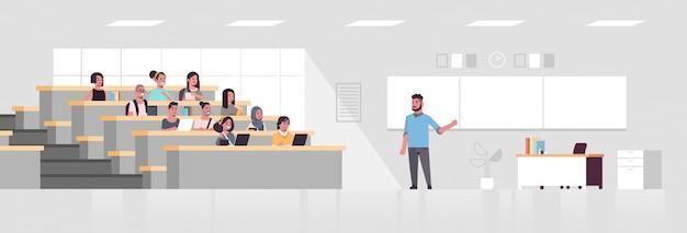 大学講堂に座っていると黒板教育概念現代教室インテリアフルレングス水平で大学男性教授に耳を傾ける学生