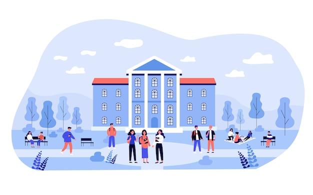 대학 건물 근처 캠퍼스에서 시간을 보내는 학생들