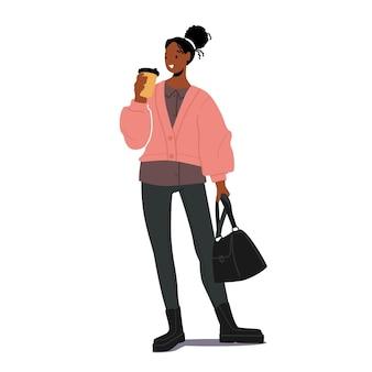 秋のシーズンに流行の服を着てコーヒーとハンドバッグを持つスタイリッシュなアフリカの女の子。女性のための秋のファッショントレンド