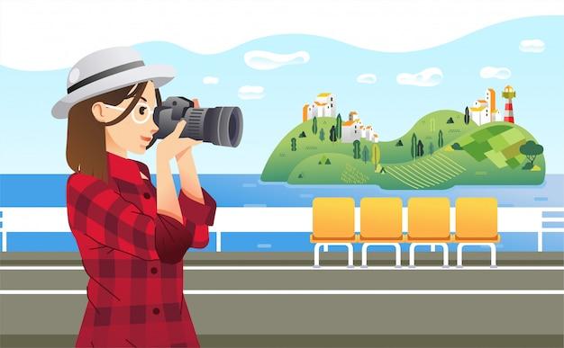 船から海の島の写真を撮るスタイリッシュな女の子の写真家