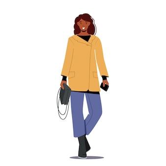 トレンディな秋の服のショートコート、ジーンズ、バッグを身に着けているスタイリッシュな女の子。女性のための秋のファッショントレンド、ファッショナブルな服