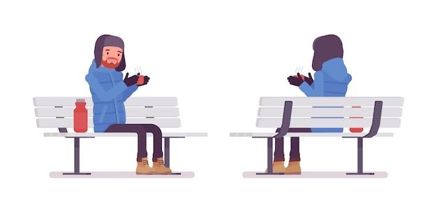 ベンチに座っている青いダウンジャケットのスタイリッシュな男