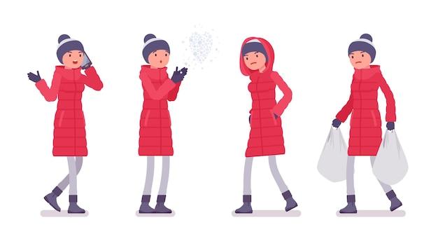通りの長い赤いダウンジャケットのスタイリッシュな女性