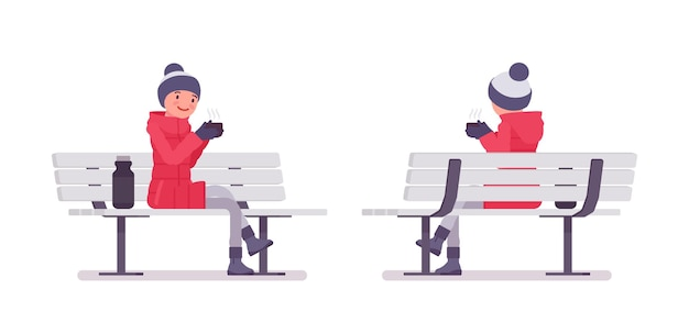 ベンチに座っている長い赤いダウンジャケットのスタイリッシュな女性