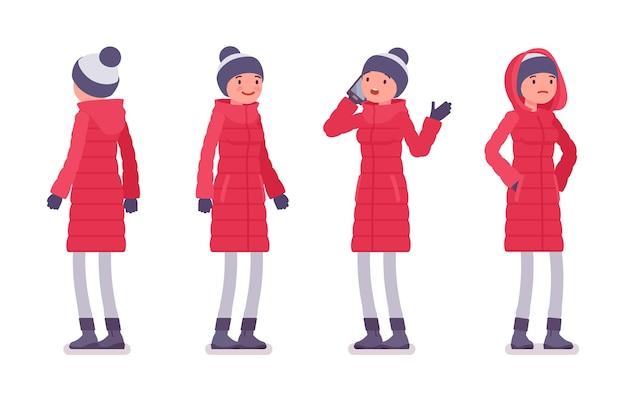 立っている長い赤いダウンジャケットのスタイリッシュな女性
