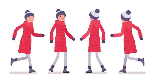 ウォーキングとランニングの長い赤いダウンジャケットのスタイリッシュな女性