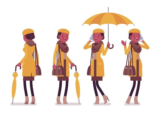 秋の服のイラストを身に着けている傘を持つスタイリッシュな若い黒人女性