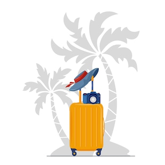 Suitcase with summer hat and camera under the palm trees