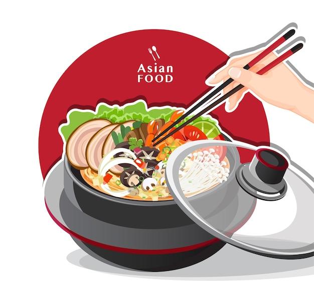 Sukiyaki in hot pot at restaurant, hand holding chopsticks eating shabu