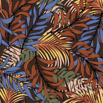 Summer abstract seamless pattern with colorful tropical leaves and plants on a brown background