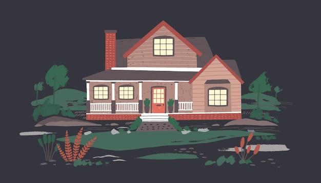 어둠 속에서 아름다운 자연으로 둘러싸인 현관이있는 여름 별장 또는 저택