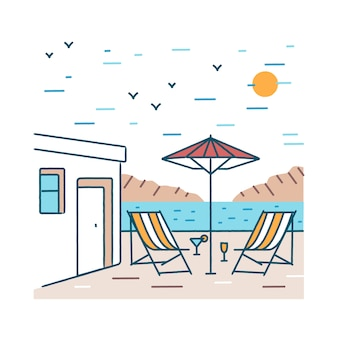 Summer landscape with pair of deck chairs, exotic cocktails and umbrella standing near hotel building against mountains and sea on background.