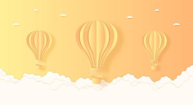 明るい空と雲、紙のアートスタイルで飛んでいる夏、オレンジと黄色の熱気球