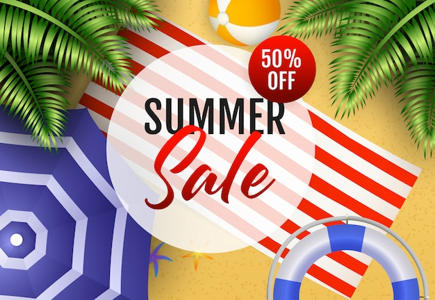 Summer sale lettering with beach ball, mat and umbrella