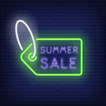 Summer sale neon sign. creative lettering inside of green tag on dark blue brick wall. night bright