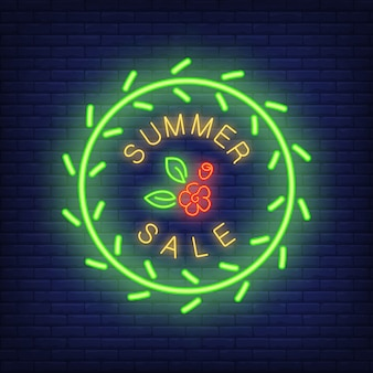 Summer sale neon sign. Glowing text in round frame, green wreath and red flower. Night bright billbo
