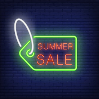 Summer sale text on tag in neon style. green sale tag with red text on dark brick wall.