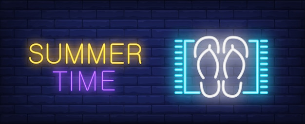 Summer time neon style lettering. flip flops on beach mat on brick background.