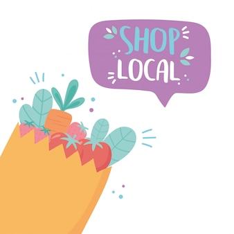 地元のビジネスをサポートし、野菜や果物が入った小さな市場の紙袋を買う