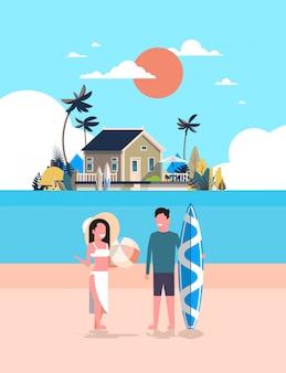 Surfer couple summer vacation man woman surf board on sunset beach villa house tropical island vertical