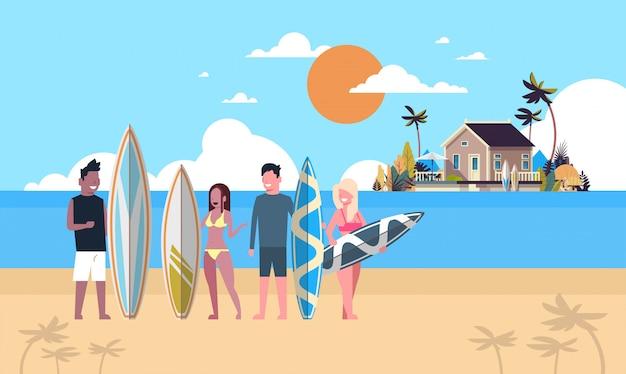 サーファーチームの夏の休暇の人々グループサンセットビーチヴィラの家熱帯の島でサーフィンボード