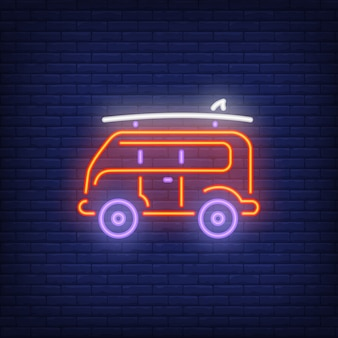 Surfer van neon sign. Retro bus with surfboard on roof on dark brick wall background.