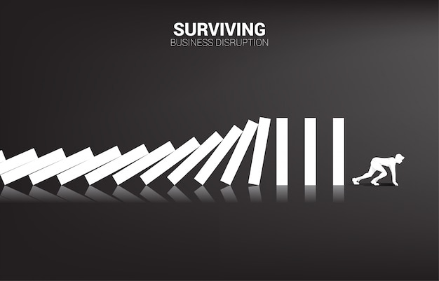 Surviving business disruption. silhouette of businessman ready to run away from domino collapse. business industry disrupt