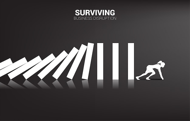 Surviving business disruption. silhouette of businesswoman ready to run away from domino collapse. concept of business industry disrupt