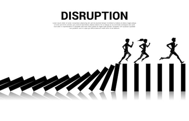 비즈니스 중단 생존. 도미노 붕괴에서 달리는 사업가와 사업가의 실루엣. 비즈니스 산업 혼란의 개념