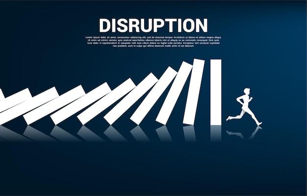 비즈니스 중단 생존. 사업가의 실루엣은 그래프 배경으로 도미노 붕괴에서 도망칩니다. 비즈니스 산업 혼란의 개념