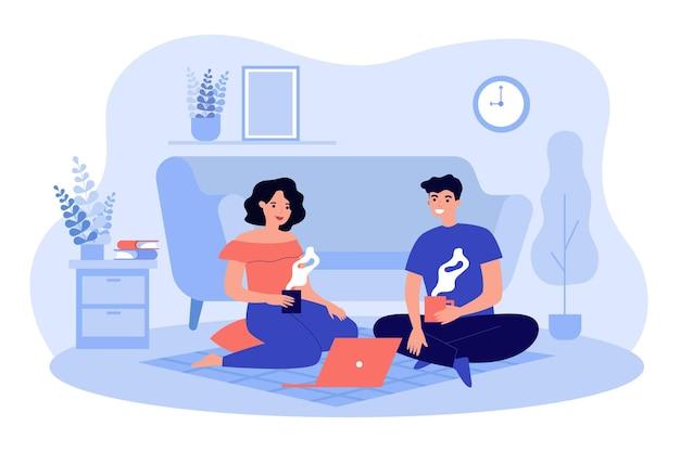 Сладкая парочка сидит на полу за ноутбуком в квартире, пьет чай или кофе, разговаривает, смотрит фильм