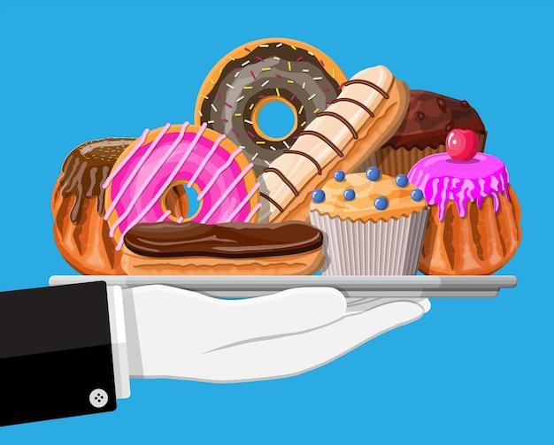 Сладкие десерты в подносе в руке. вкусная еда. кондитерские изделия или хлебобулочные изделия. эклер, пончик, маффин. шоколадные коржи с заварным кремом и ягодами.