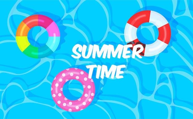 カラフルな救命浮環のあるプールの夏夏の時間
