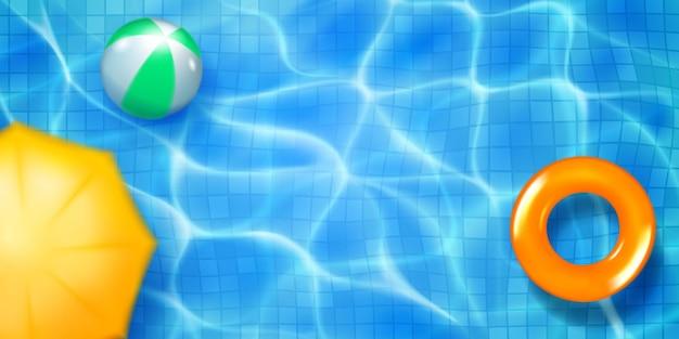 モザイクタイル、インフレータブルリング、ボール、日よけのあるスイミングプールの上面図。日光のまぶしさと苛性波紋のある水色の水面。夏休みの背景。