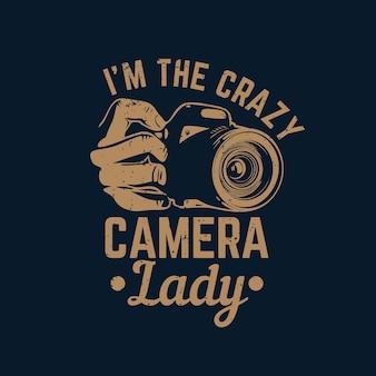 Tシャツのデザイン私はカメラと紺色の背景のビンテージイラストを持っている手で狂ったカメラの女性です