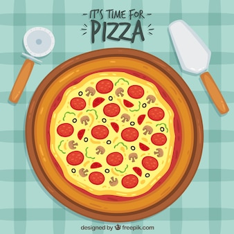 Tablecloth background with delicious pizza and salami
