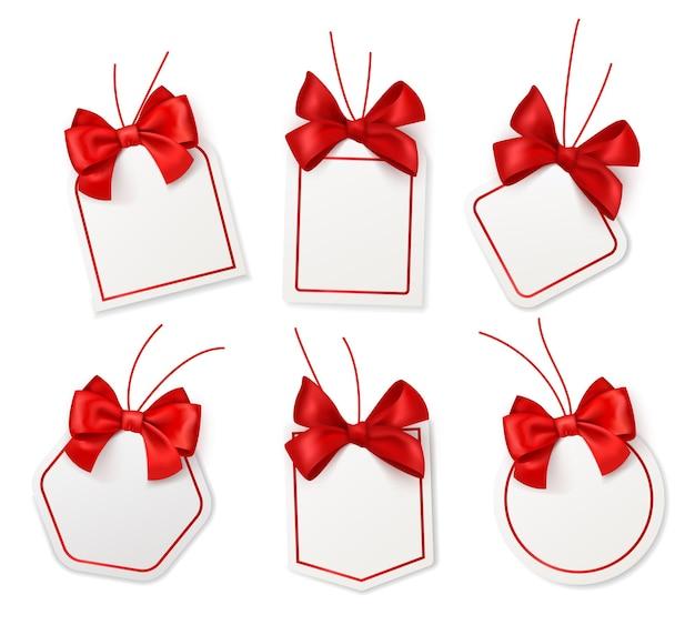 Бирки с красными бантами. пустые белые ценники с шелковыми алыми лентами на рождество, день рождения или свадьбу, подарочная упаковка, вектор, реалистичная коллекция изолированных шаблонов