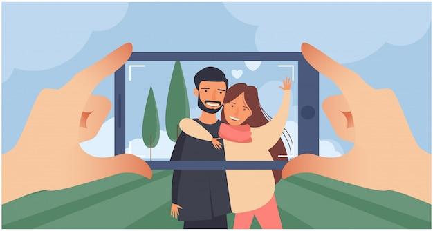 スマートフォンで写真を撮る。風景を背景に笑顔のカップル。横の写真。スマートフォンを持っている手