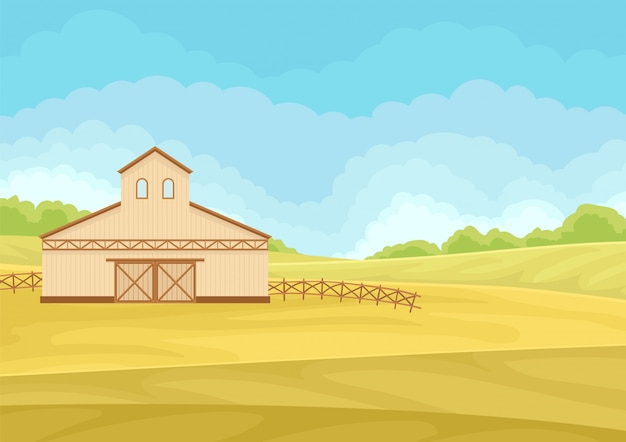 Tall beige barn with closed gate in the field.