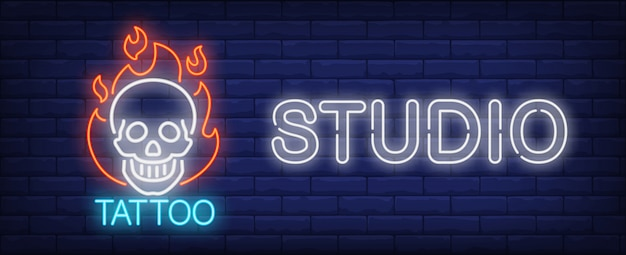 Tattoo studio neon sign. smiling scull on fire and big inscription on dark brick wall.