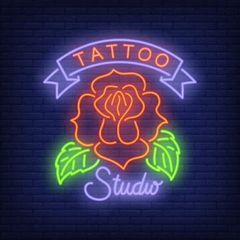 Tattoo studio neon sign with rose. Night bright advertisement, colorful signboard