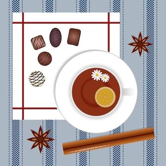 シナモンとアニスのティーカップと青いテーブルクロスの背景にチョコレート菓子。図。上面図