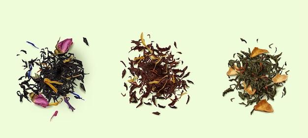 Vista dall'alto di cumuli di tè, assortimento di foglie secche e fiori