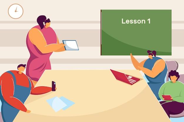 Учитель и ученики используют гаджеты на уроке. плоские векторные иллюстрации. дети сидят в классе за столом, глядя на компьютер, смартфоны. образование, обучение, школа, концепция технологии