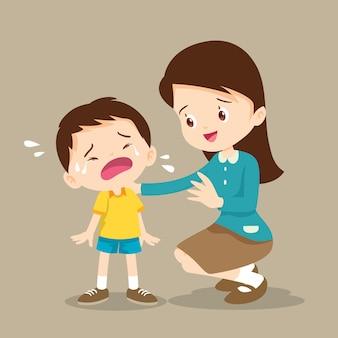Teacher comforting crying boy