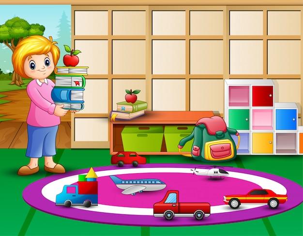 幼稚園の部屋で子供のための本を持っている先生