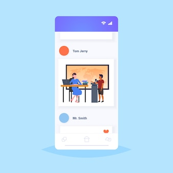 Teacher with pupil schoolboy speaking at world map geography lesson at school education concept modern classroom full length smartphone screen online mobile application