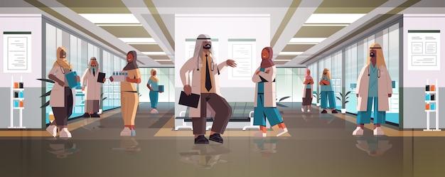 病院の廊下での会議中に話し合う制服を着たアラビア語医師のチーム医学ヘルスケアの概念水平全長ベクトル図