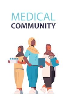 アラビア語の医療専門家のチームは、制服を着たアラブの女性医師が一緒に立っている医学ヘルスケアの概念垂直全長ベクトル図